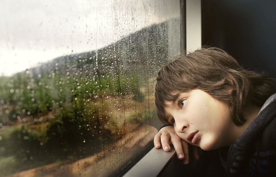 Bored child looking out of a raindrop covered window