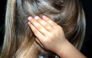 Child with hands over ears