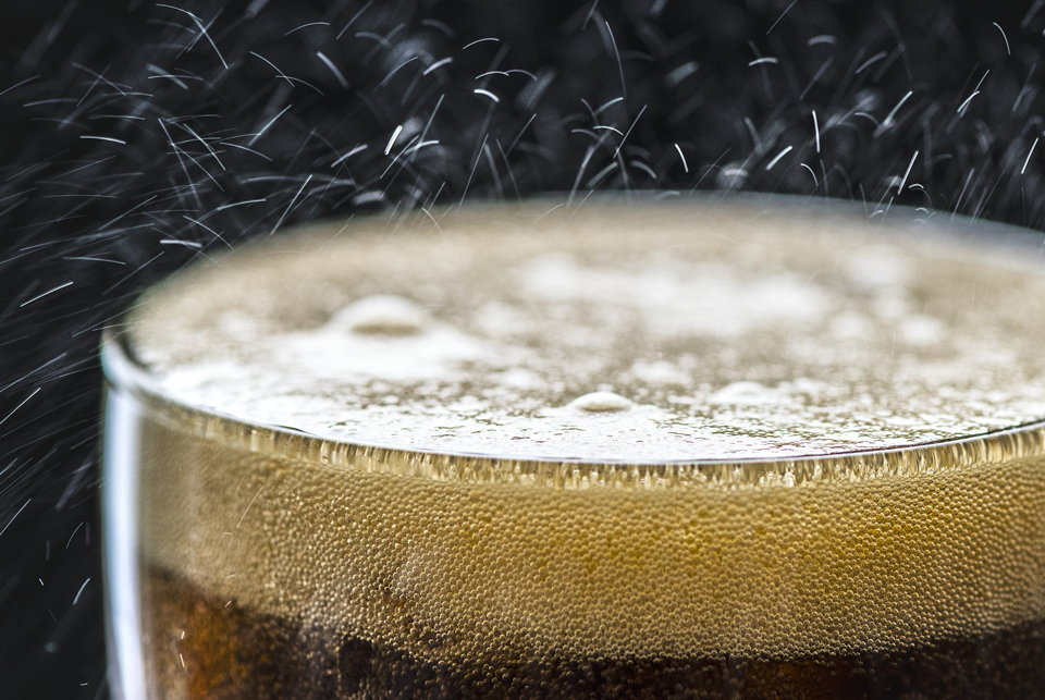 Close-up of the top of a carbonated drink in a glass