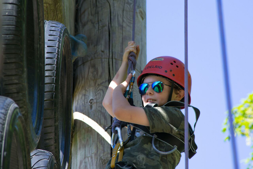 Boy climbing a vertical obstacle course