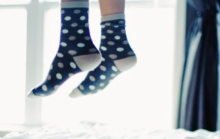 Child's feet in socks bouncing on the bed by Rafael Lodos