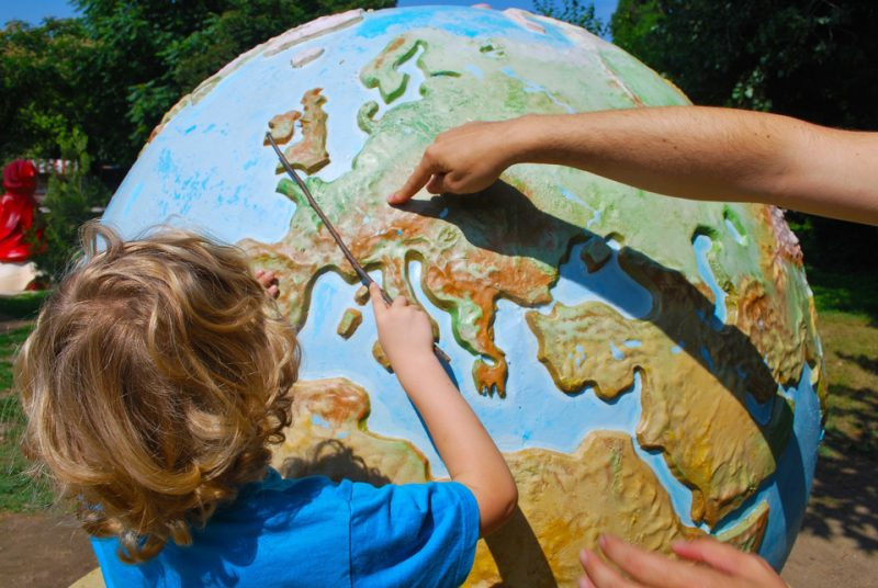 Small boy being shown the world on a large globe