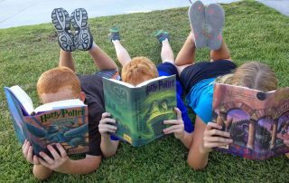 three children lying on the grass reading Harry Potter books