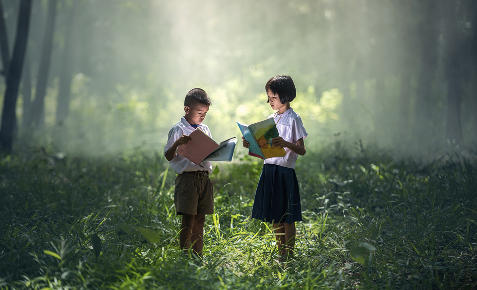 Two children standing in a forest reading books