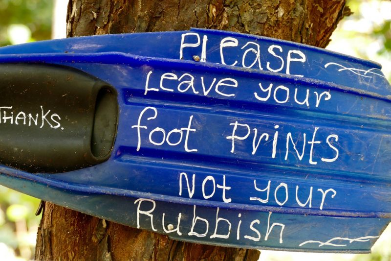 Leave footprints not rubbish written on piece of plastic stuck in a tree