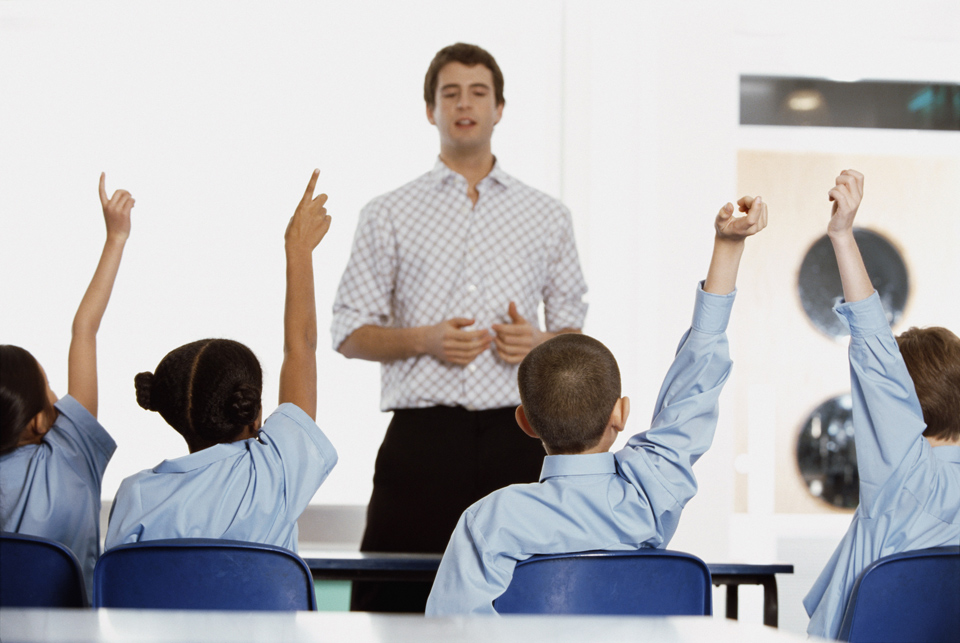 Kids raising hands in a classroom