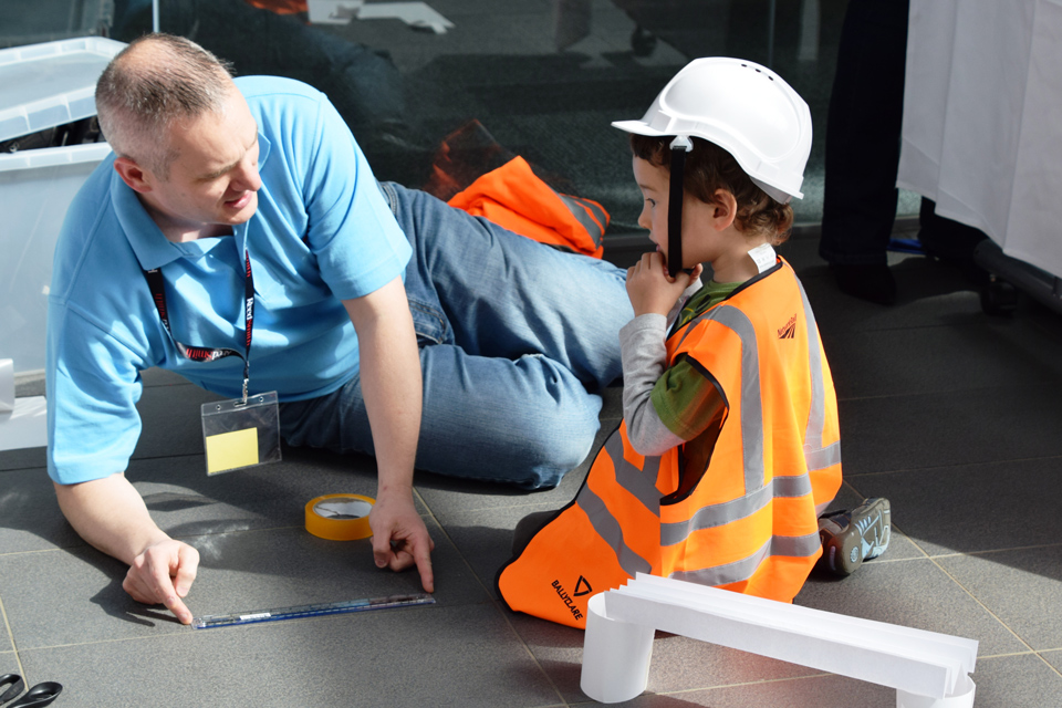 Man working on the floor with a child dresses as a mini engineer