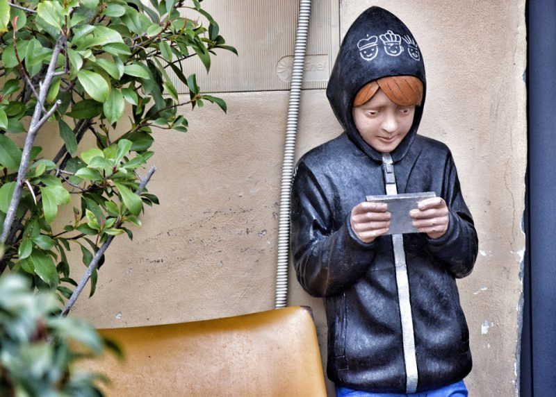 statue of a child in a hoodie looking at a mobile
