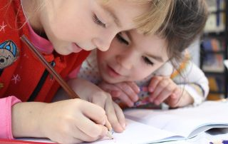 2 young girls leaning together over some work, collaborating