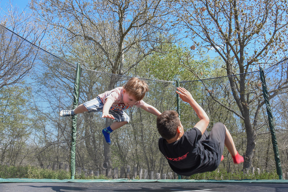 2 kids bouncing on a trampoline