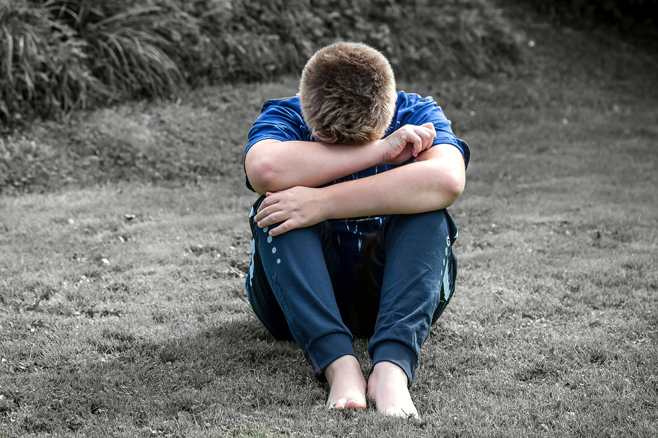 Boy sitting with his head in his arms