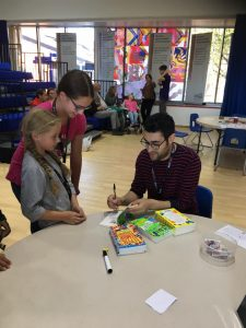 Joshua Seigal signing his poetry books at Potential Plus UK's Big Family Weekend, 2018