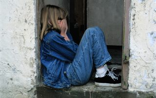 Child sitting in a doorway with hands over her face