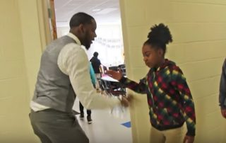 Teacher Mr White giving a personalised hi five greeting to individual students