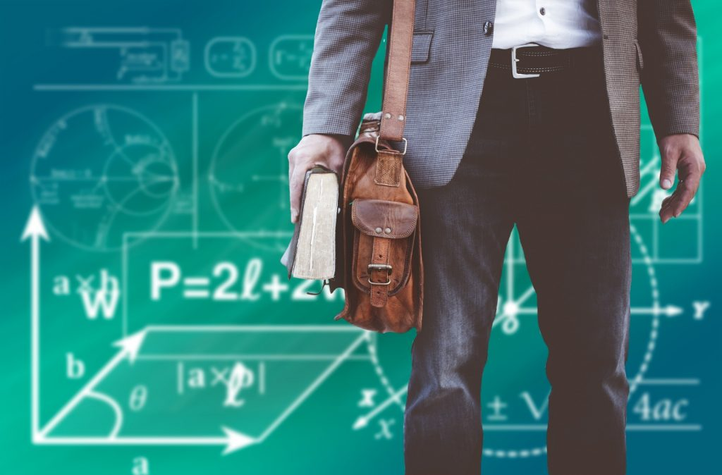 Man standing in front of a blackboard full of equations