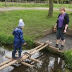 Girl crossing a stream on a pole bridge she helped build at the PPUK Be Curious Weekend 2019