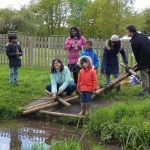 Families working together to create a pole bridge across the stream at the PPUK Be Curious Weekend 2019