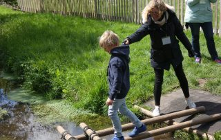 Child testing the bridge they built across a stream at the PPUK Be Curious Weekend 2019