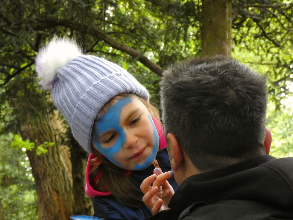 "Girl applying ""wode"" facepaint to her father at the PPUK Be Curious Weekend 2019"