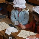 Two girls dressed in victorian mobcaps practising copperplate handwriting at the PPUK Be Curious Weekend 2019