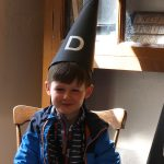 Boy wearing a dunce's hat in the Victorian Classroom at PPUK Be Curious Weekend 2019