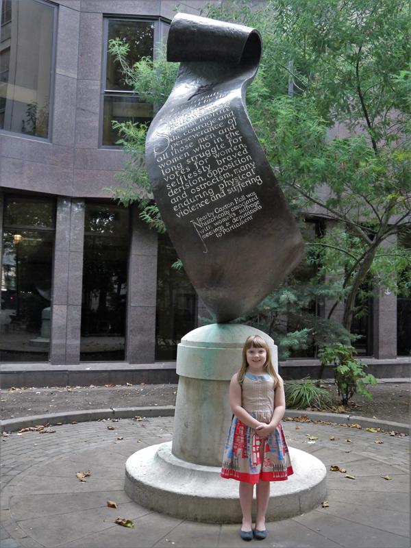 Girl standing underneath the Suffragette memorial in Christchurch Gardens