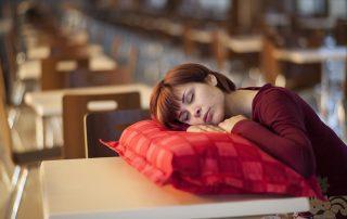 Lady asleep with head on a cushion that is resting on a teacher's desk