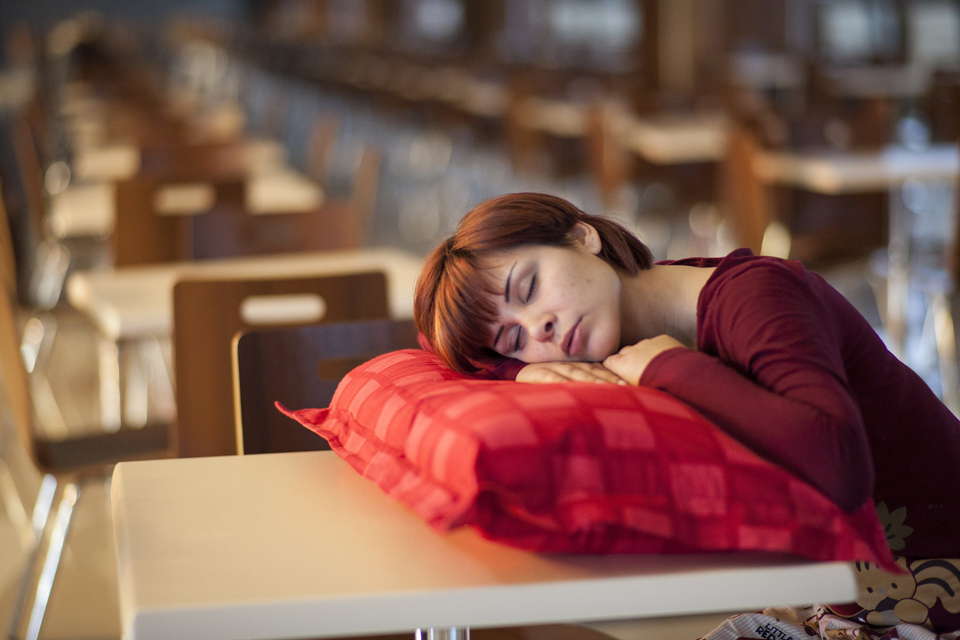 Lady asleep with head on a cushion that is resting on a teacher's desk
