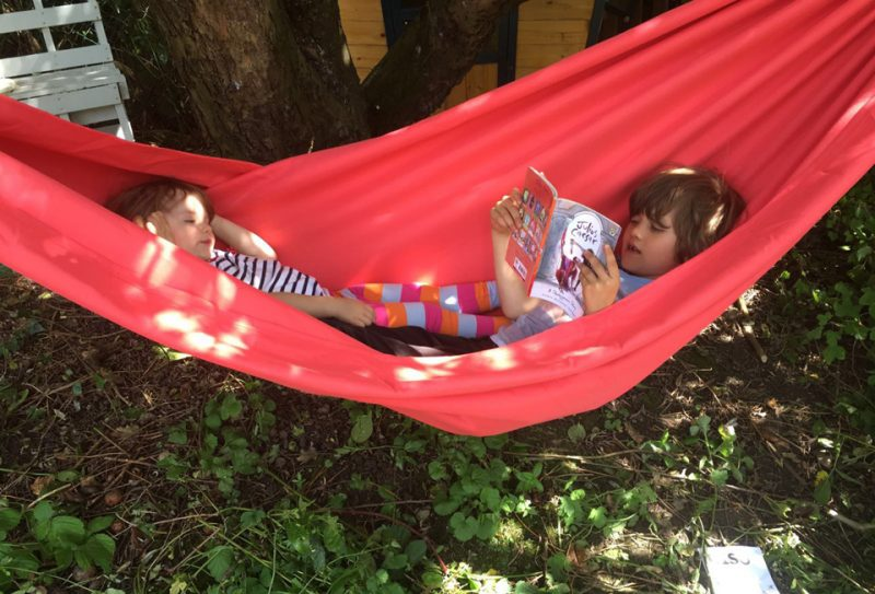 Noah, aged 6, reading Shakespeare to Rosa, aged 2 in a red hammock