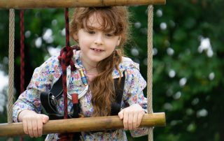 Girl climbing up a rope ladder