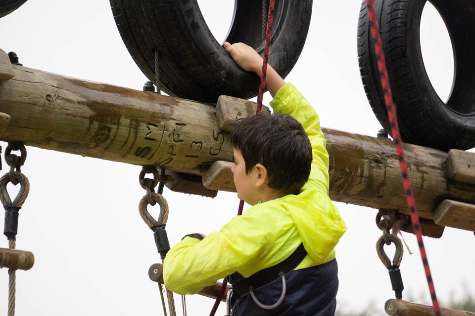 boy climbing an outdoor obstacle course
