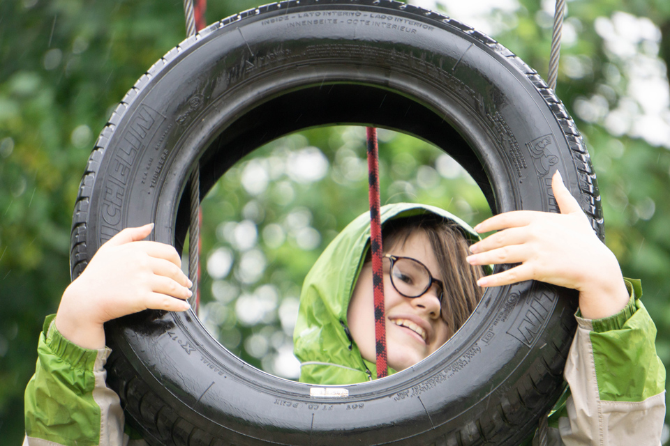 girl with face viewed through a tyre