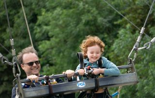 father and daughter on a giant outdoor swing