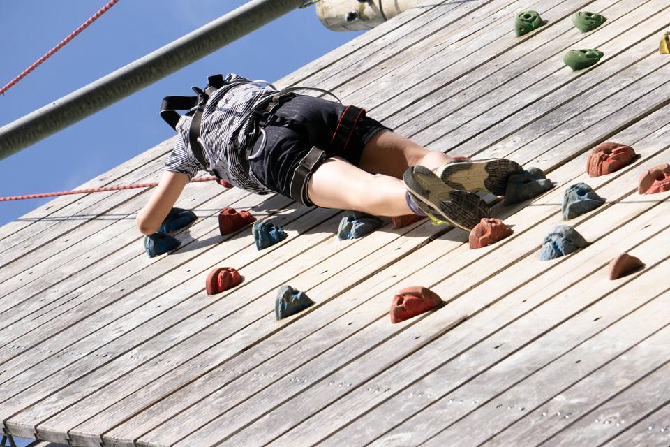 Boy high on a climbing wall
