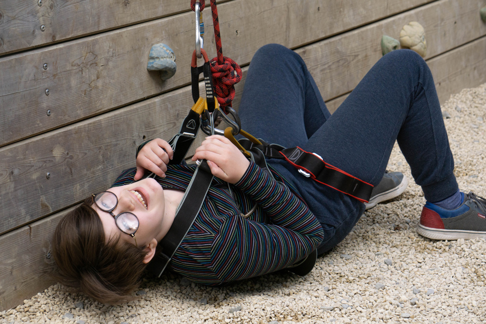 Girl lying on her back in a harness