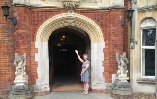 Julie Taplin standing with arms in a welcoming stance outside the entrance door to The Mansion, Bletchley Park, July 2019