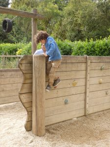 child climbing over an obstacle wall