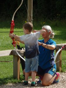 young boy being helped to fire an arrow
