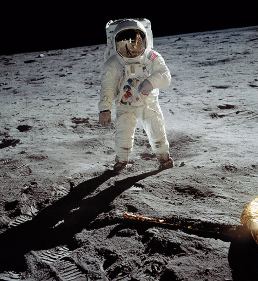 Buzz Aldrin on the surface of the moon photographed by Neil Armstrong who is reflected in the helmet