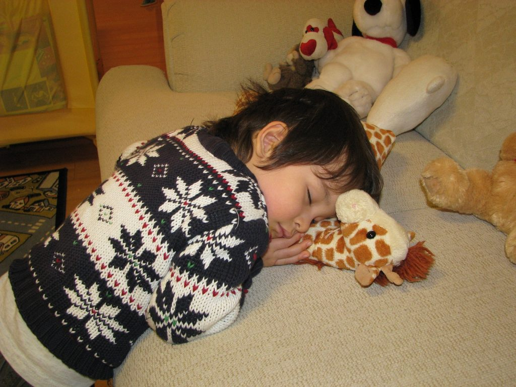 Child asleep on the sofa hugging a soft toy giraffe
