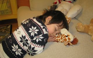 Child asleep on the sofa hugging a soft toy giraffe