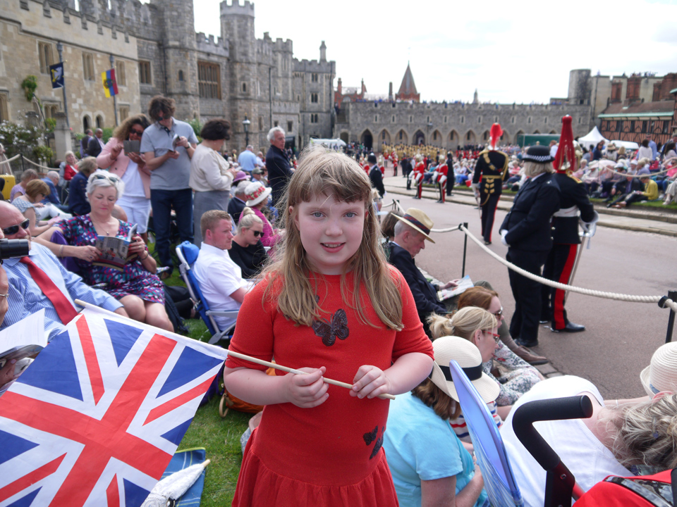Girl holding a Union Jack flag in the crowd watching the procession at Garter Day 2019