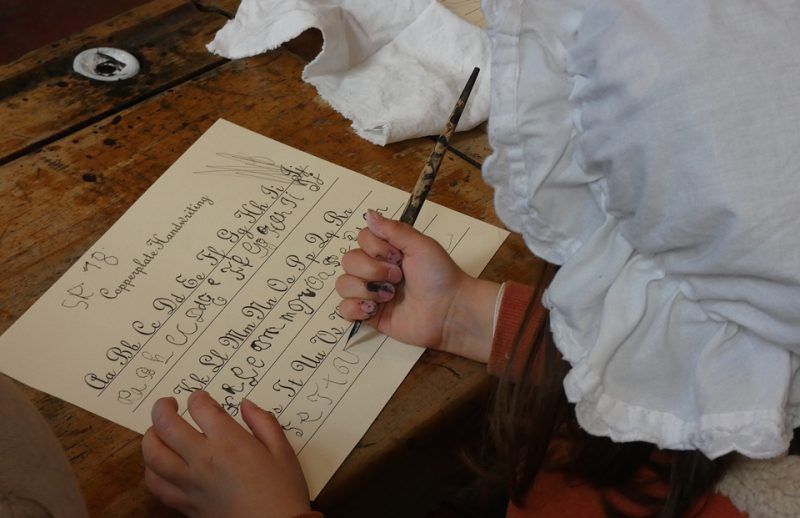 Child dressed in victorian mopcap doing copperplate handwriting practice
