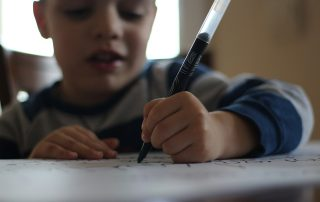 Boy writing with a pen