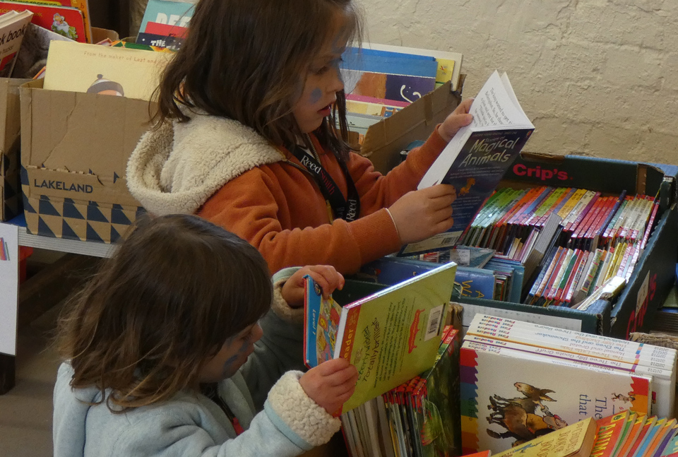 two young girls looking through and reading books from boxes