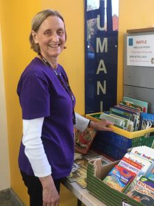 Volunteer Hilary Ramsden running the book stall at Potential Plus UK's BIG Family Weekend, 2019