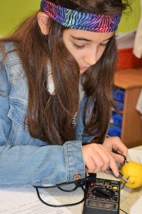 Girl measuring electricity generated by a lemon Potential Plus UK's BIG Family Weekend, 2019