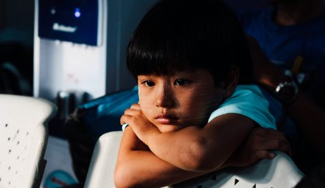 Child leaning on the back of a chair looking unhappy