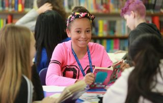 Smiling Girl in Library at Parliament Hill School. Copyright Parliament Hill School, London