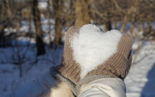 gloved hands holding snow shaped into a heart